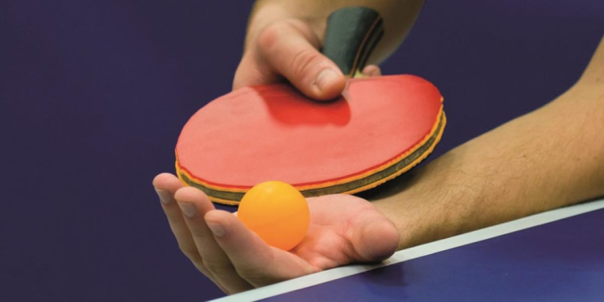 table tennis bat and ball in players hand