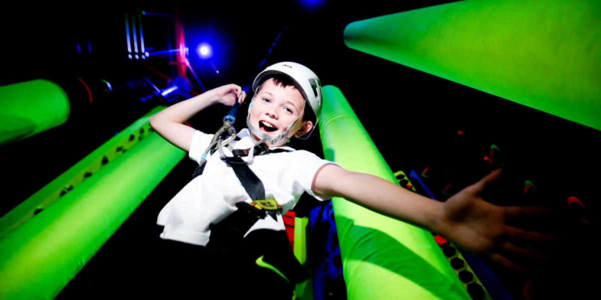 Boy on Blacklight climbing wall at Ards Blair Mayne